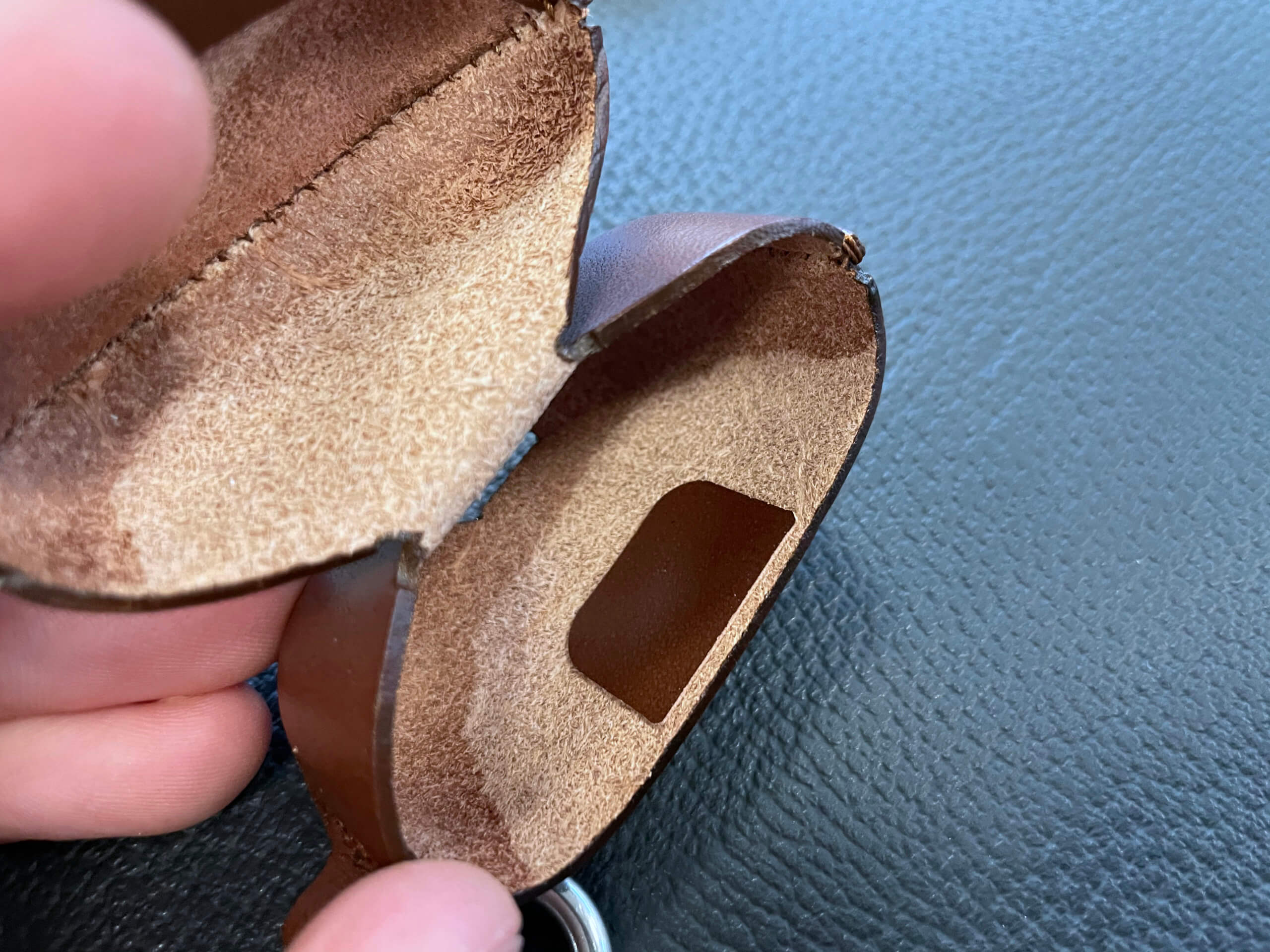 The small scrap of leather covers aggressive metal parts of the button.