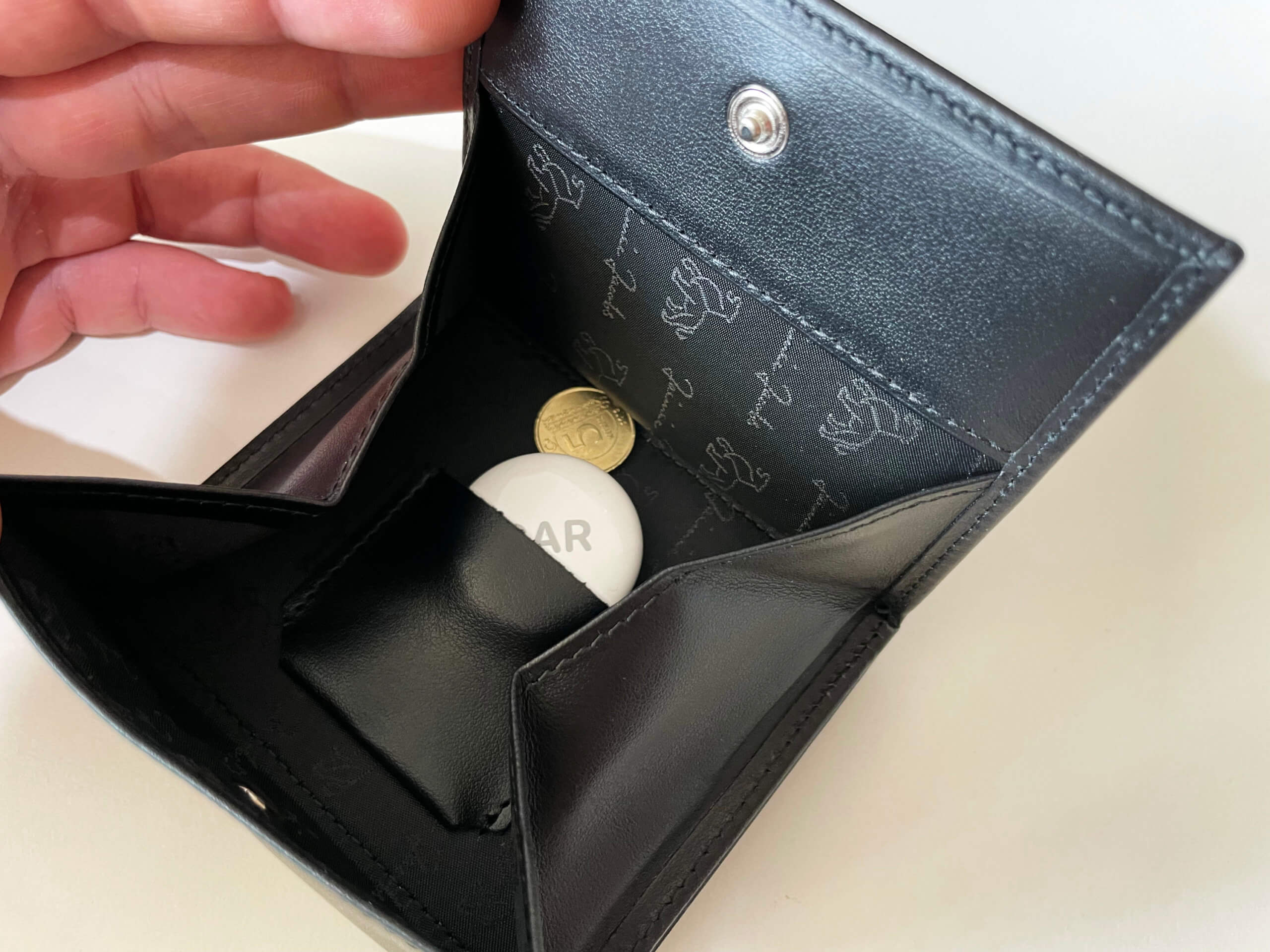 Der AirTag lässt sich in einem separaten Täschchen im Münzfach verstauen.